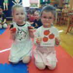 Dwie dziewczynki są na zdjęciu. Jedna trzyma planszę z nazwą papryką po angielsku, a druga trzyma paprykę w rączce