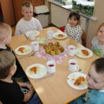 Dzieci przy stolikach jedzą obiad