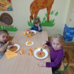 Dzieci przy stolikach spożywają obiad