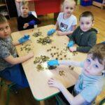 Dzieci z grupy motylków liczą pieniążki