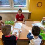 Dzieciaki Mleczaki chłopcy z grupy Pszczółki odszukują różnice w obrazkach przedstawiających krowy i kolorują je