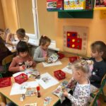 Dzieciaki Mleczaki dzieci z grupy Biedronki wycinają z gazetki produkty mleczne