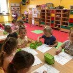 Dzieciaki Mleczaki dzieci z grupy Pszczółki odszukują różnice w obrazkach przedstawiających krowę i kolorują je