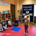 Dzieciaki Mleczaki dziewczynka z grupy Biedronki z zawiązanymi oczami degustuje napój mleczny