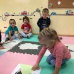 Dzieciaki Mleczaki dziewczynka z grupy Bratki rozszyfrowują ukryty obrazek