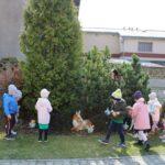 Przedszkolaki szukaja w krzewach ukrytych prezentow