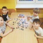 chłopcy układają puzzle