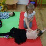 dzieci na dywanie w pozycji bocznej