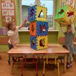 dziewczynki układają wysoką wieżę z klocków piankowych