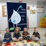 dzieci siedzą na dywanie przed tablicą