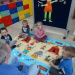 11. dzieci siedzą na dywanie wykonują ćwiczenie - energiczne ziewanie