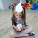 dziewczynka tworzy slomką pianę mydlaną