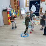 dzieci biegają po sali w rym padajacego deszczu