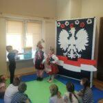 Dzieci przebrane w stroje karkowskie przy tablicy orła