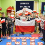 Dzieci trzymaja flagę Polski