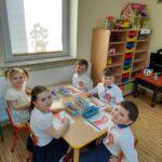 Dzieci wykonuja zadania przy stolikach