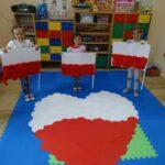 Dzieci z flagami Polski i wielkim biało-czerwonym sercem