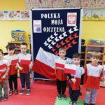 Dzieci z flagami przy tablicy patriotycznej