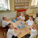 Dzieci z grupy żabek wykonują zadanie przy stolikach