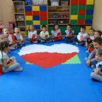 Dzieci z ułożonym na macie wielkim biało-czerwonym sercem