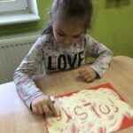 Dziewczynka pisze palcem w kaszy POLSKA