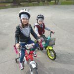 Dziewczynka z bratem jeżdżą na rowerach