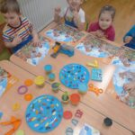 Żuczki przy stole z kolorową plasteliną
