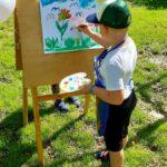 Chłopiec maluje na sztaludze