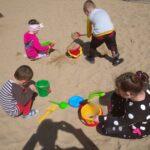 Dzieci bawią się na przedszkolnym placu zabaw, zabawy z wykorzystaniem nowych zabawek terenowych