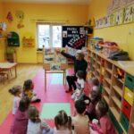 Dzieci oglądają obrazki i słuchają opowiadania pani