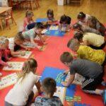 Dzieci wykonują zadania na macie- podpisywanie obrazków wyrazami