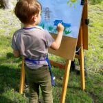 Dziecko maluje farbami w parku