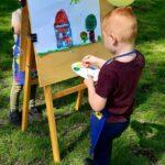 Dziecko z grupy Mrówki maluje w plenerze