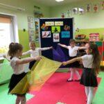 Dziewczynki tańczą z kolorowymi chustkami