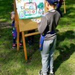Przedszkolak maluje farbami w plenerze