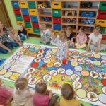 Przedszkolaki grają w dużą grę planszową