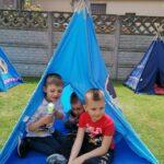 Chłopcy siedzą w wigwamie
