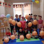 Dzieci siedzą na macie z balonami