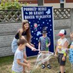Dzieci z nauczycielką robią bańki mydlane