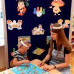 Dziewczynka z nauczycielką grają w grę planszową