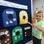 Chłopczyk segreguje odpady na zajęciach