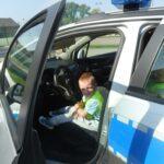 Chłopczyk siedzi na miejscu kierowcy w radiowozie policyjnym