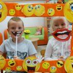 Chłopiec i dziewczynka uśmiechają się używając akcesorii w ramce z buziek