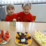 Dwie dziewczynki siedzą przy stoliku z owocami