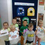 Dzieci pozują z śmietniczkami zrobionymi na zajęciach