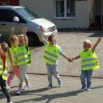 Dzieci przechodzą przez jezdnię z uniesioną ręką