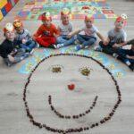 Dzieci siedzą nad uśmiechnietą buzią z kasztanów