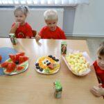 Dzieci siedzą przy stolikach