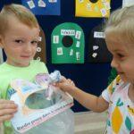 Dzieci wrzucają papier do woreczków wykonanych na zajęciach