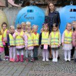 Dzieci z nauczycielką przy koszach na śmieci